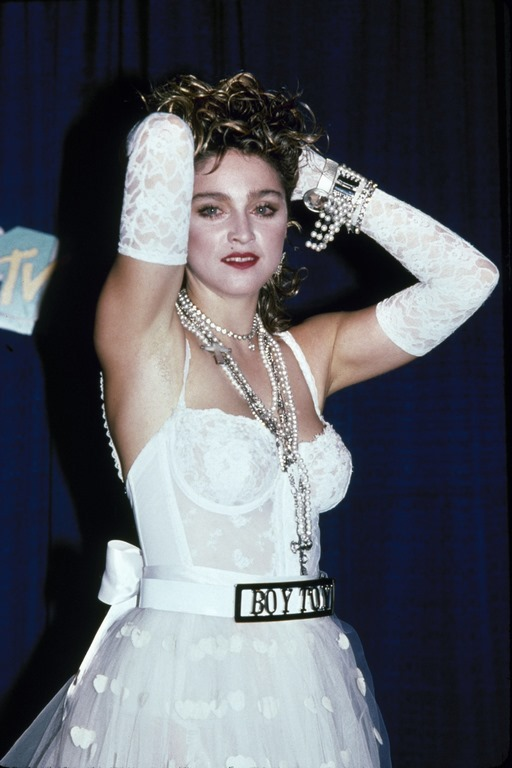 American singer and actress Madonna, dressed in white lace lingerie, pearls, and a 'Boy Toy' belt buckle, stands with her arms on her head at First Annual MTV Video Music Awards, held at Tavern on the Green, New York, New York, September 14, 1984. (Photo by David Mcgough/DMI/The LIFE Picture Collection/Getty Images)