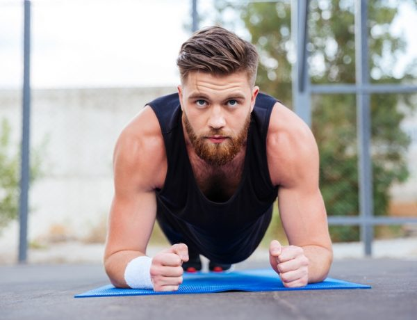 Sportsman doing plank exercise on blue fitness mat during workout