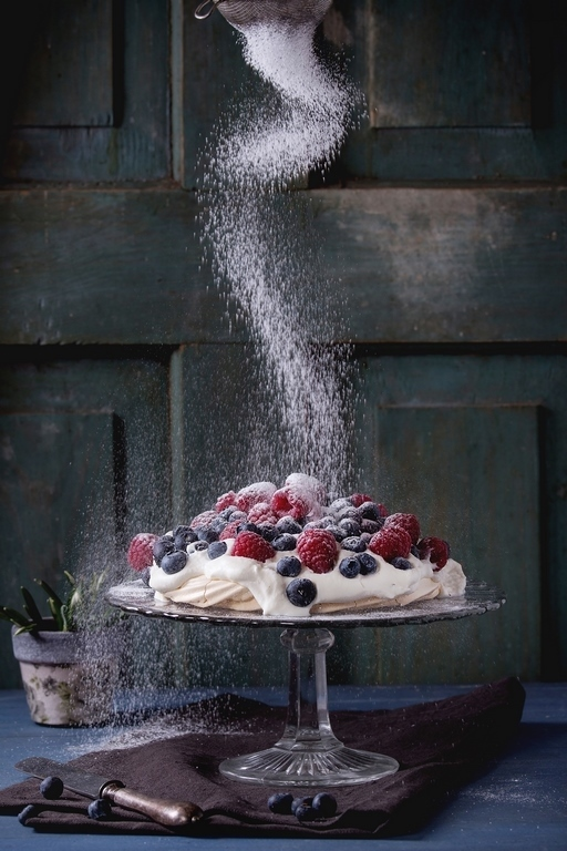500px Photo ID: 139471969 - Vintage cake stand with Meringue dessert Pavlova with fresh blackberries and raspberries, strewing by sugar powder. Over blue wooden table. Dark rustic style.
