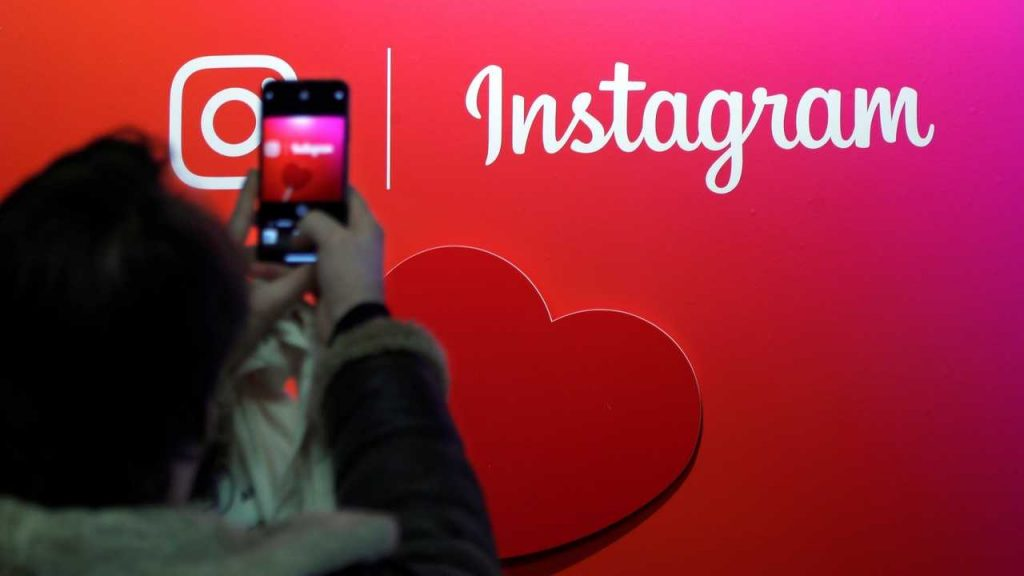 A visitor takes a picture of the Instagram application logo at the Young Entrepreneurs fair in Paris, France, February 7, 2018. REUTERS/Charles Platiau - RC17CE29E2E0